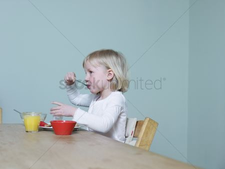 Interior background : 4-5 year old sits eating breakfast