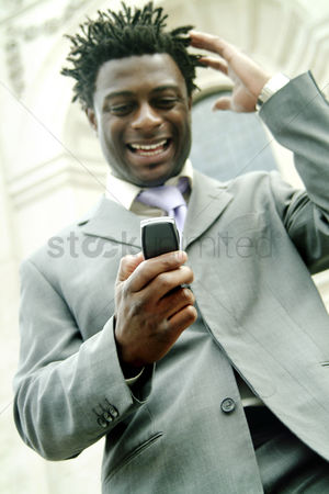 Funny : A african american man in business suit laughing at the message he received