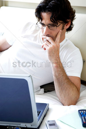 Cell phone : A bespectacled man lying on the bed reading his work on the laptop