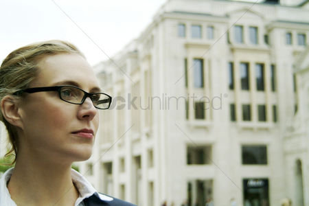 Determined : A bespectacled woman standing in front of a building