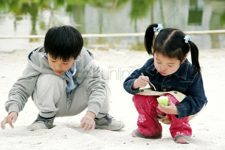 Young boy : A boy and a girl squatting on the lakeside playing with sand