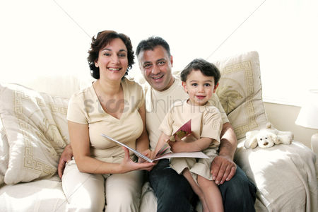 Young boy : A couple sitting on the couch reading a book for their young son