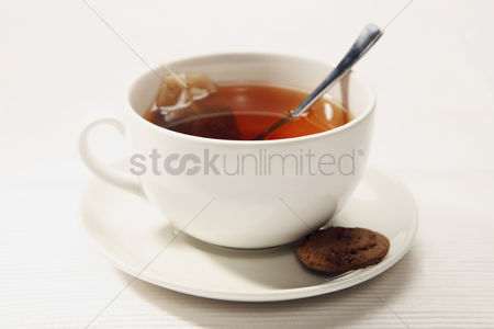 Indulgence : A cup of tea with biscuit at the side