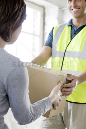 Jacket : A friendly delivery man passing over a parcel to customer