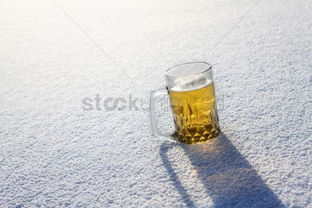 Cold temperature : A glass of beer sitting in snow