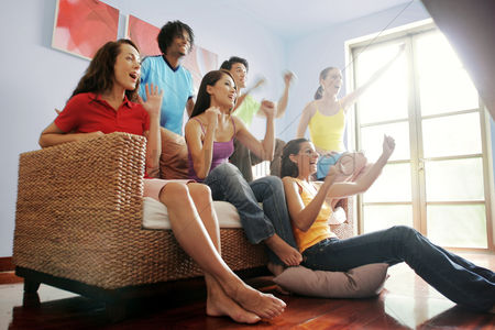 Match : A group of friends cheering while watching football match on the television