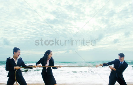 Business suit : A guy playing tug of war on the beach with two ladies