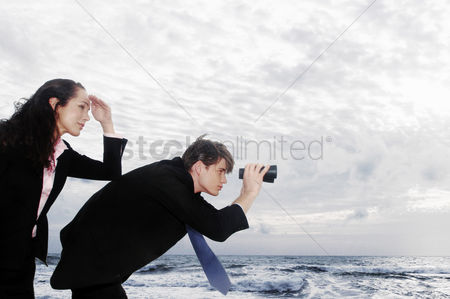 Girlfriend : A guy using a binocular to look at the sea view whiles his girlfriend using her hand to shade herself