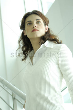Stairs : A lady in white blouse standing on the stairs leaning on the handrail