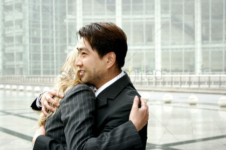 Sales person : A man and a woman in business suits hugging