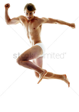 Strong : A shirtless man in white underwear jumping with his hands opened