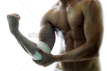 Body : A shirtless muscular man with a bandage on his elbow