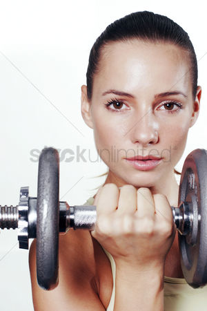 Strong : A woman holding up a dumbbell