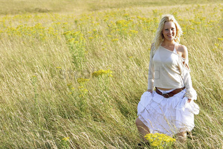 Having fun : A woman standing on the prairie holding her long skirt