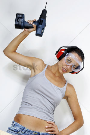Goggle : A woman with goggles and headphone raising a driller above her head