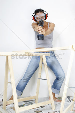 Goggle : A woman with goggles and headphone using a driller to shoot at the camera