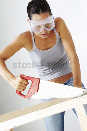 Goggle : A woman with goggles sawing a wood