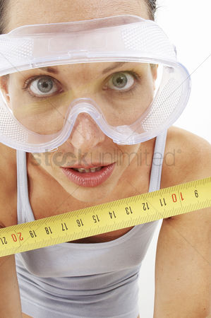 Goggle : A woman with goggles using a measuring tape to measure the camera