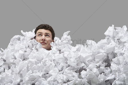 Pile : Adult man covered in crumpled paper looking up