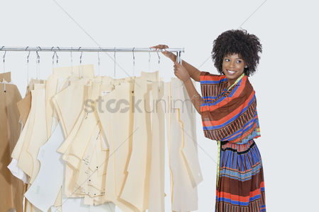 Traditional clothing : African american female designer with sewing patterns on clothes rack over gray background