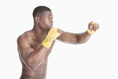 Arts : African american male boxer kickboxing over gray background