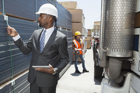 Land : African american male engineer inspecting planks while female worker standing by flatbed truck