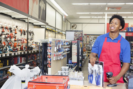 Supermarket : African american male store clerk at checkout counter in super market