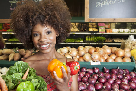 Curly hair : African american woman holding bell peppers and vegetables at supermarket