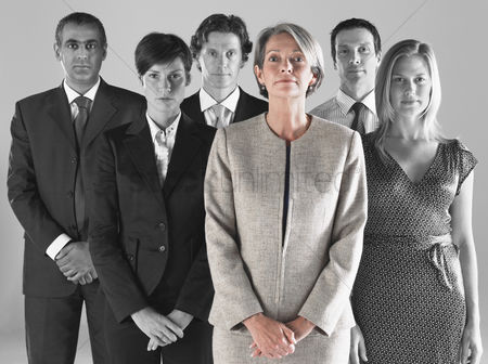 Leadership : Ambitious businesswoman with team of professionals against gray background