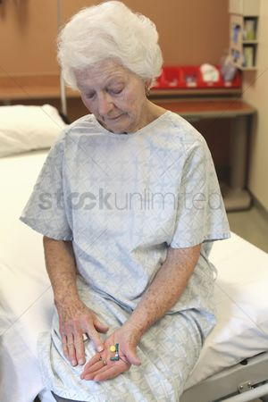 Medication : An old lady in a hospital gown  sitting on a bed  looking down at several pills in her hand