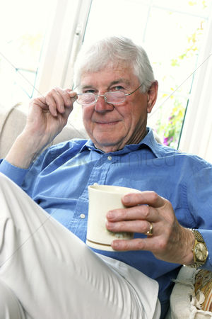 Bespectacled : An old man adjusting his spectacle while holding a cup of coffee