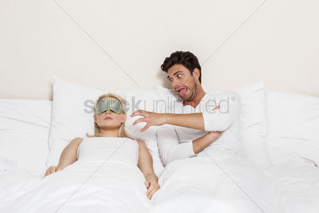 Funny : Angry young man teasing sleeping woman in bed