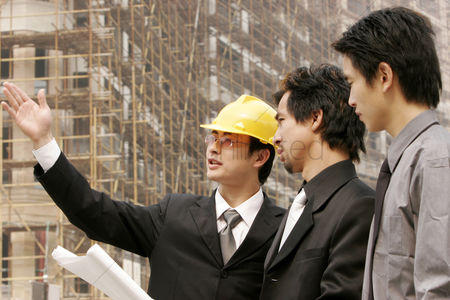 Office worker : Architect discussing a building plan with his client at a construction site