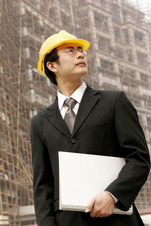 Bespectacled : Architect holding a document at a construction site