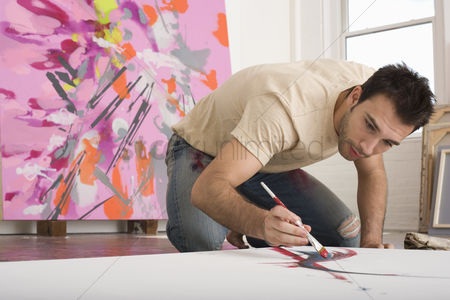Arts : Artist working on canvas on floor of studio
