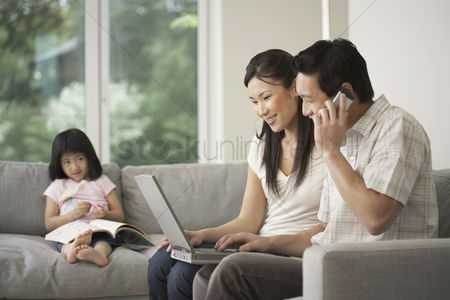 Young boy : Asian couple using laptop on sofa with daughter watching in background