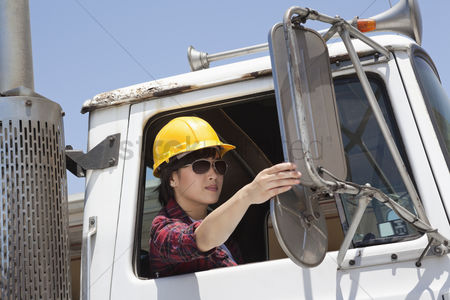 Land : Asian female industrial worker adjusting mirror while sitting in logging truck