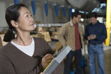 Interior background : Asian woman making notes in distribution warehouse