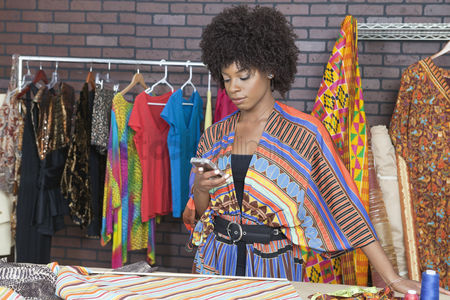 Traditional clothing : Attractive african american female fashion designer using cell phone
