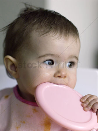 Adorable : Baby girl biting a container s cover