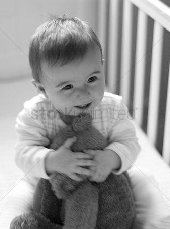Children playing : Baby girl playing with her teddy bear in the crib