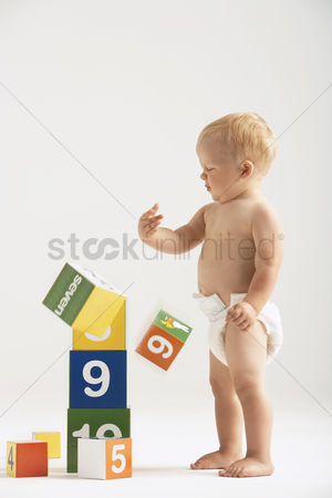 Children playing : Baby knocking over blocks