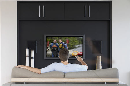 Remote : Back view of mid-adult man changing channels with television remote control in living room