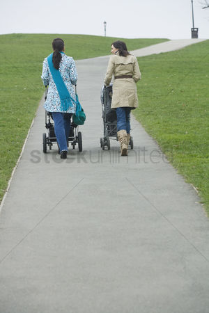 Pushing : Back view of two mothers pushing strollers in park