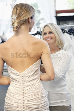 Elegance : Back view of woman dressed in bridal gown with happy senior owner assisting