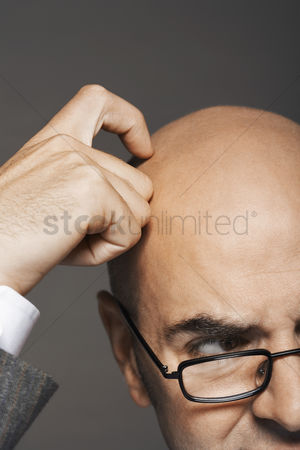 Bald : Bald businessman wearing glasses scratching head high section