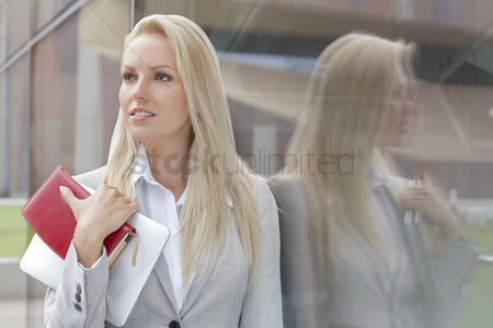 Employee : Beautiful businesswoman holding organizer and digital tablet while looking away by glass wall