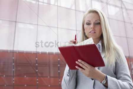 Employee : Beautiful businesswoman reading notes in organizer while standing against office building
