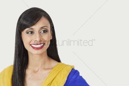 Traditional clothing : Beautiful indian woman looking sideways over gray background