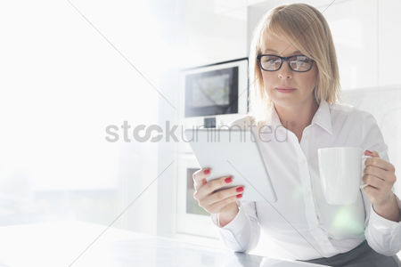 Internet : Beautiful mid adult businesswoman having coffee while using table pc at home